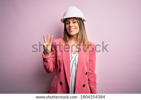 Young beautiful brunette architect woman wearing safety helmet over pink background showing and pointing up with fingers number three while smiling confident and happy.