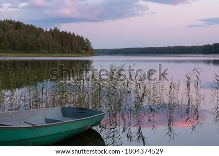 Beautiful sunset view on the lake with symmetrical reflections in the water of pink clouds and a fishing boat on the shore
