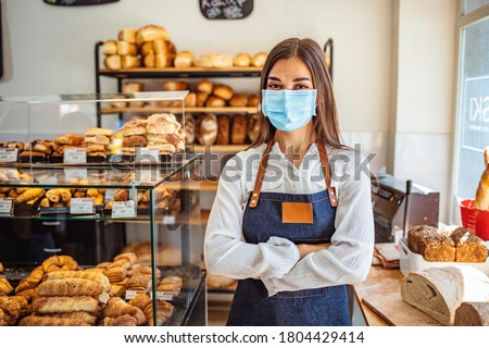 Woman working at a bakery wearing a facemask to avoid the coronavirus. COVID-19 lifestyle concepts. Day in the life of owners of bakery shop with the protocol against the Covid-19 in place.  #1804429414