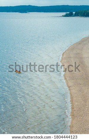 Minimal picture of scenic sand beach coast line of Ladoga lake island in Karelia with two people in kayak in water and pine forest in background shot from a high point