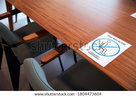 Social distancing sign in office on meeting room table. Royalty-Free Stock Photo #1804473604
