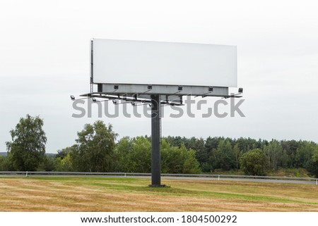 Large commercial megaboard, billboard standing in a field next to road and trees on a skyline with empty blank space gray sky background.