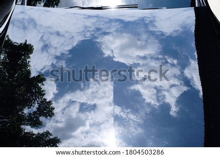 The reflection of clear sky on black car hood & bonnet after car wash & ceramic coat. Car detail and paint protection concept. Shiny car background. Top view. Royalty-Free Stock Photo #1804503286
