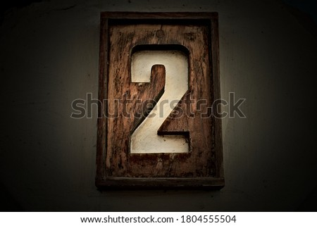 Number 2, two, a light digit on dark and vignetted background.