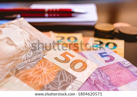 Real, money from Brazil. Dinheiro, Brasil, Reais, Real brasileiro. A group of Real banknotes and coins on a table. #1804620571