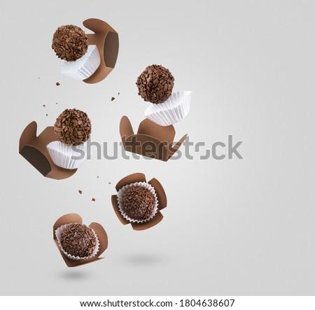 Brigadeiro (Brigadeiro), a Brazilian chocolate candy. Traditional Brazilian handmade chocolate candy. Falling in motion on gray background. Royalty-Free Stock Photo #1804638607