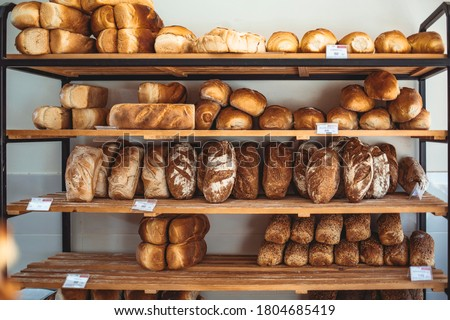 Fresh bread on shelves in bakery. Delicious loaves of bread in a german baker shop. Different types of bread loaves on bakery shelves. Modern bakery with assortment of bread #1804685419