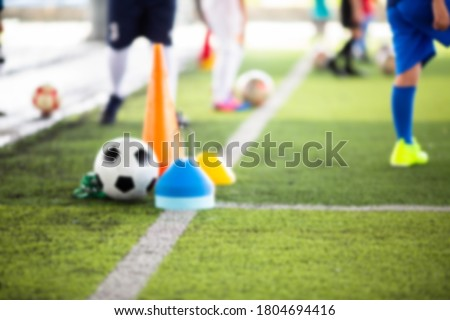 Blurry picture of sport background. Soccer ball with kid soccer player and soccer training equipment on green artificial turf and mini goal in soccer academy.