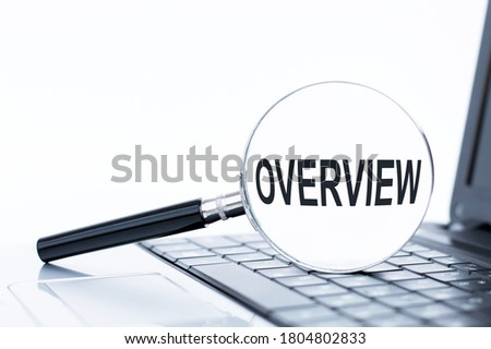 OVERVIEW text on the magnifying lying on the laptop keyboard Royalty-Free Stock Photo #1804802833