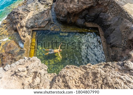 A young man enjoying a natural sea pool in the cove of Puerto de Puntagorda, island of La Palma, Canary Islands. Spain Royalty-Free Stock Photo #1804807990