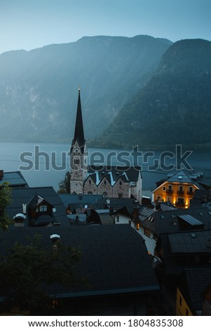 The famous small old town of Hallstatt with moody dark winter weather with fog. Travel place to visit in Austria. Pictures view of the church in Halltatt at the lake, Salzkammergut in Austria