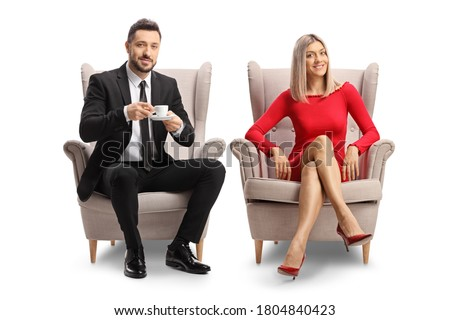 Young blond woman in a red dress  and a man with a cup of coffee sitting in armchairs isolated on white background Royalty-Free Stock Photo #1804840423