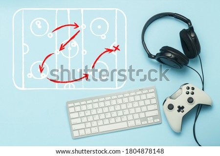 Keyboard, headphones and gamepad on a blue background. Added drawing with the tactics of the game. Hockey. The concept of computer games, entertainment, gaming, leisure. Flat lay, top view.