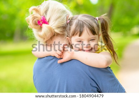 Mother and little girl with syndrom down have a fun in summer park Royalty-Free Stock Photo #1804904479