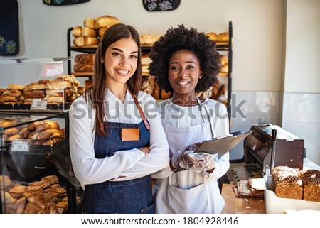 Two beautiful young bakers at the bakery. Shot of two women holding a selection of freshly baked breads in their bakery. Nobody bakes it better than we do