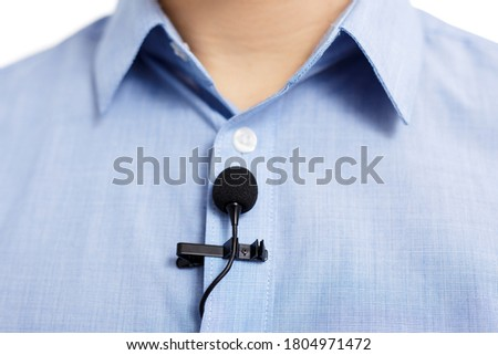 broadcasting and sound recording concept - close up of small lavalier clip-on microphone on blue male shirt
