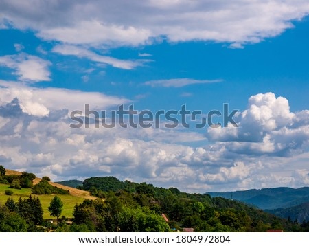 Cumulus congestus or towering cumulus - forming in the blue sky over hilly landscape Royalty-Free Stock Photo #1804972804