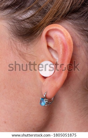 A Woman with Earplug Into Her Ear Close-up