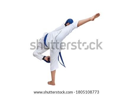 On white isolated background in karategi boy athlete performs a kick #1805108773