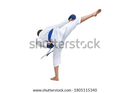 On white isolated background in karategi boy athlete kicks kick Royalty-Free Stock Photo #1805115340