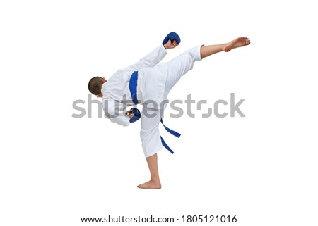 In karategi athlete with blue belt performs a kick on white isolated background Royalty-Free Stock Photo #1805121016