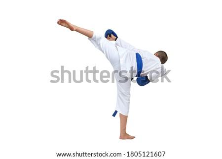 Athlete in karategi with blue belt beats kick kick on white isolated background Royalty-Free Stock Photo #1805121607