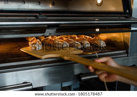 Close up of baker is taking off from oven the french baguette bread with wood peel at baking manufacture factory. French baguette bread bakery factory concept. #1805178487