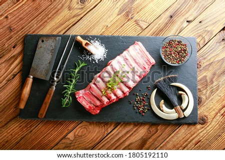 Detail on raw meat, on the ribs of wild boars on a black plate with rosemary, marjoram, salt and pepper. the atmosphere of hunting is completed by weapons from wild boar. #1805192110