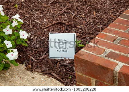 Close up image of a funny and creative yard sign on the front yard of a house that reads: This is a Private Sign, Do not Read.'