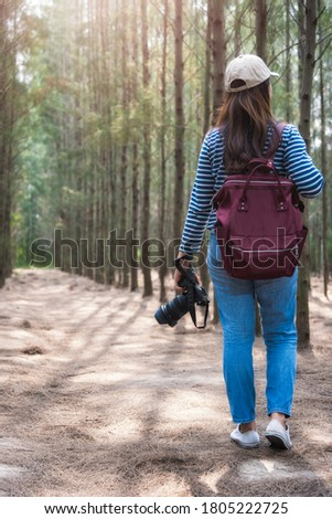 Female woman lifestyle use camera photographer travel taking shooting photo in forest nature and backpack and copy space