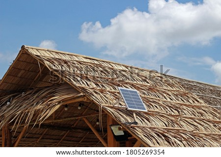 A solar panel on the roof of a thatched hut against blue sky and clouds. Royalty-Free Stock Photo #1805269354