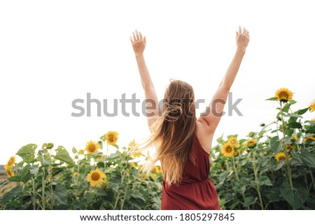 Rear view of young blond woman with arms raised enjoying her freedom in sunflower field against sky. High quality photo