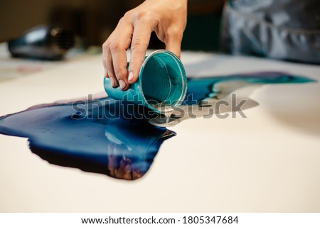 Girl artist pouring paint on paper making an art picture close up Royalty-Free Stock Photo #1805347684