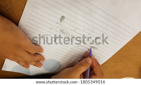 a woman writing 2021 HAPPY NEW YEAR script text hand lettering on a paper. Design template Celebration typography poster, banner or greeting card for Merry Christmas and happy new year.