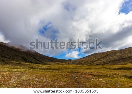 Clouds rolling over high-altitude tundra in glacial valley in the Chugach Mountains, Aaska