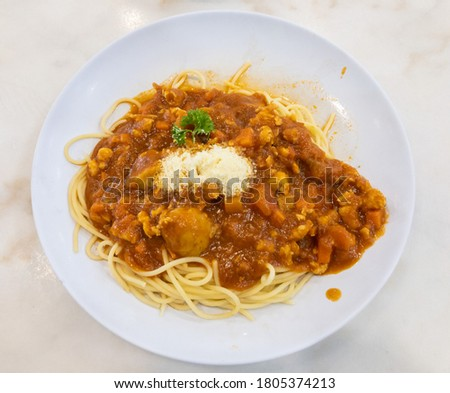 Spaghetti pasta with meatballs and tomato sauce on a white plate. Delicious food. Top view.