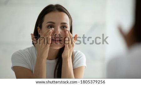 Close up smiling young woman wearing white t-shirt doing facial massage, applying moisturizing cream on under eye skin, looking in mirror, standing in bathroom, enjoying skincare procedure Royalty-Free Stock Photo #1805379256