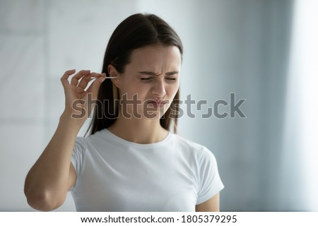Close up young woman cleaning ears, using cotton bud after shower, feeling pain, beautiful female wearing white t-shirt standing in bathroom, morning routine, personal hygiene concept Royalty-Free Stock Photo #1805379295