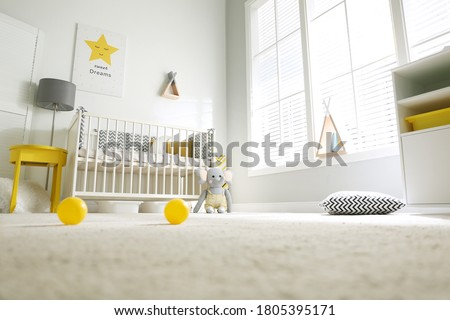 Cute baby room interior with crib and big window, low angle view Royalty-Free Stock Photo #1805395171