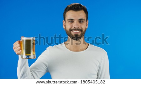 Young man drinking beer, showing beer and smiling at camera.Portrait of young male staring lovingly at beer.