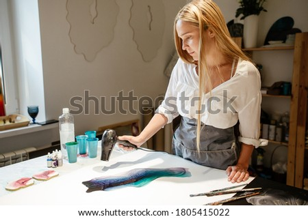 Artist dries paint with a hair dryer creating an art picture, standing in front of a table in a home Studio