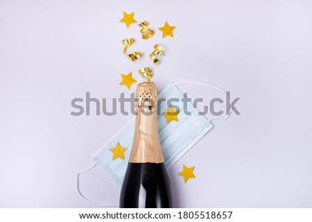 Bottle of Champagne Gold Confetti in Shape of Star Protective Face Mask on Blue Background New Year 2021 Celebration Concept Top view Flat lay #1805518657
