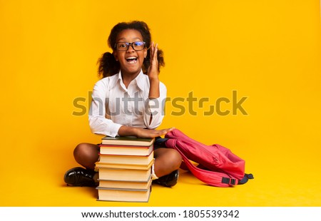 Back To School. Nerdy Schoolgirl Raising Hand During Class Sitting At Books Over Yellow Studio Background. Free Space