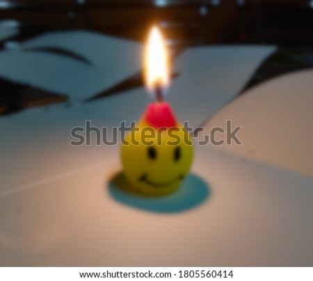 Blur candle on wooden table with black Blurred background, Bokeh of light, Burning candle lights on a dark background, happy birthday concept background.