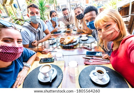 Friends taking selfie at coffee bar - New normal lifestyle concept with young people having fun together at restaurant cafe covered by face masks - Bright vivid filter Royalty-Free Stock Photo #1805564260