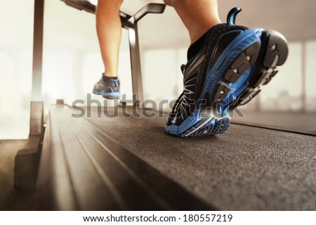 Man running in a gym on a treadmill concept for exercising, fitness and healthy lifestyle #180557219