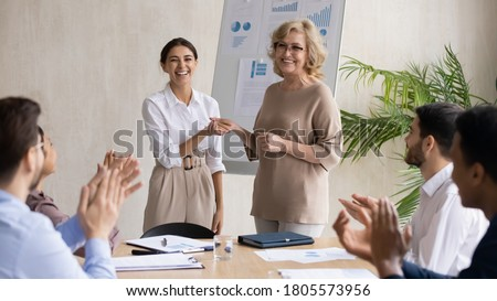 Smiling middle aged 60s female company leader shaking hands with happy young arabic colleague, praising for good work or thanking for good job done at briefing meeting with diverse employees. Royalty-Free Stock Photo #1805573956