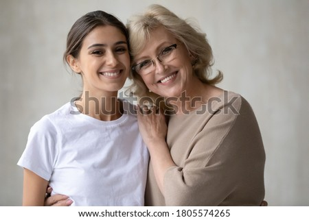 Head shot portrait of smiling multiracial different female generations family. Happy 60s european mother in eyeglasses cuddling shoulders of attractive young 30s arabic ethnicity grown up daughter.