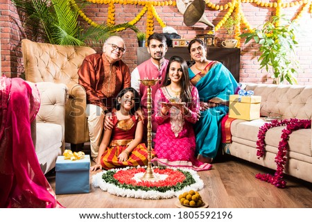 Happy Indian Family Celebrating Ganesh Festival or Chaturthi - Welcoming or performing Pooja and eating sweets in traditional wear at home decorated with Marigold Flowers #1805592196