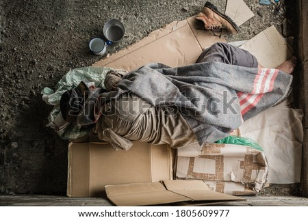 Old homeless man wearing sweater and blanket sleeping on cardboard seeking help because hungry and food beggar from people walking pass on street. Poor man homeless and depression concept. #1805609977